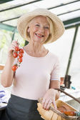 Woman in greenhouse holding cherry tomatoes smiling — Stock Photo