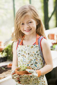 Young girl in greenhouse holding potted plant smiling — Stock Photo