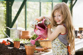 Young girl in greenhouse watering potted plant smiling — Stock Photo