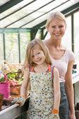 Mladá dívka a žena ve skleníku s úsměvem — Stock fotografie