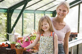 Young girl and woman in greenhouse smiling — Stock Photo