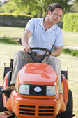 Man outdoors driving lawnmower — Stock Photo