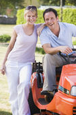 Couple outdoors with lawnmower smiling — Stock Photo
