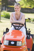 Woman outdoors with lawnmower smiling — Stok fotoğraf