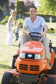 Man outdoors driving lawnmower smiling with family in background — Stock Photo
