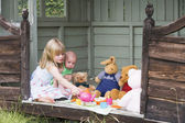 Young girl in shed with baby playing tea — Stock Photo