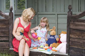 Woman and young girl in shed playing tea and smiling — Stock Photo