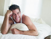 Man lying in bed smiling — Stock Photo