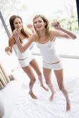Twee vrouwen springen op het bed glimlachen — Stockfoto