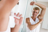 Man in bathroom applying deodorant smiling — Stock Photo