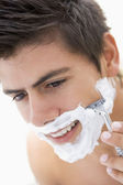 Man shaving and smiling — Stock Photo