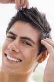 Man playing with hair smiling — Stock Photo