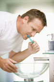Man in bathroom brushing teeth — Stock Photo