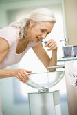 Woman in bathroom brushing teeth — Stock Photo