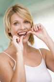 Woman flossing teeth — Stock Photo
