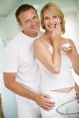 Couple in bathroom with face cream smiling — Stock Photo