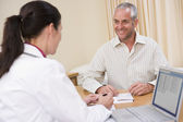 Doctor with laptop and man in doctor's office smiling — Stock Photo