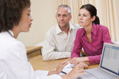 Doctor with laptop and couple in doctor's office frowning — Stock Photo