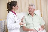 Lekarz daje sprawdzanie człowiekowi w egzamin pokój uśmiechający się — Zdjęcie stockowe