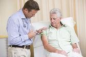 Doctor giving man needle in exam room — Stock Photo