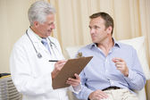 Doctor writing on clipboard while giving man checkup in exam roo — Stock Photo