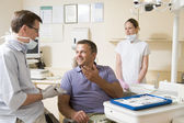 Dentist and assistant in exam room with man in chair smiling — Stock Photo
