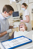Dentist and assistant in exam room with woman in chair — Stock Photo