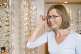 Woman trying on eyeglasses at optometrists smiling — Stock Photo