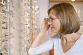 Woman trying on eyeglasses at optometrists — Stock Photo