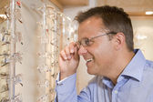 Man trying on eyeglasses at optometrists smiling — Foto Stock