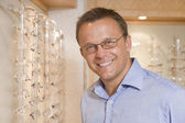 Man trying on eyeglasses at optometrists smiling — Stock Photo