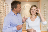 Couple trying on eyeglasses at optometrists smiling — Stock Photo