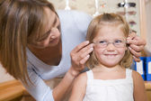 Woman trying eyeglasses on young girl at optometrists smiling — Stock Photo
