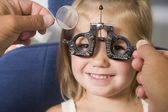 Optometrist in exam room with young girl in chair smiling — Stock Photo