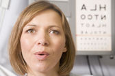 Woman in optometrist's exam room taking deep breath — Foto Stock