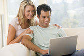 Couple in living room using laptop smiling — Stok fotoğraf