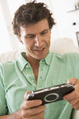 Man in living room playing handheld videogame smiling — Stock Photo