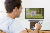 Man in living room watching television — Stock Photo