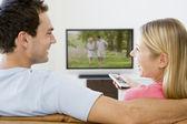 Casal na sala a ver televisão sorrindo — Foto Stock
