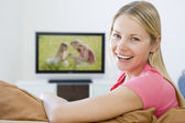 Woman in living room watching television smiling — Stock Photo