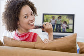 Woman in living room watching television — Stock Photo