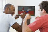 Two men in living room watching television and cheering — Stock Photo
