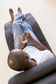 Kişisel dijital asistan kullanarak sandalyede oturan adam — Stok fotoğraf