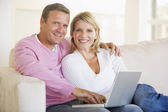 Couple in living room using laptop and smiling — Stock Photo