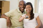 Couple in living room with remote control smiling — Stock Photo