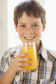 Young boy indoors drinking orange juice smiling — Stock Photo