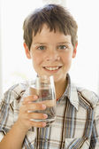 Young boy indoors drinking water smiling — Stock Photo