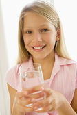Young girl indoors drinking water smiling — Stock Photo