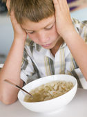 Young boy in kitchen eating soup — Stock Photo