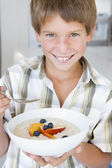 Young boy in kitchen eating oatmeal with fruit smiling — Stock Photo